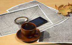 Чашка кофе на таблице рядом с старыми картами и концом-вверх лупы Стоковая Фотография RF