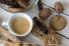 Чашка кофе, печенья, грецкий орех и шоколад на белой деревянной предпосылке Стоковое Изображение RF