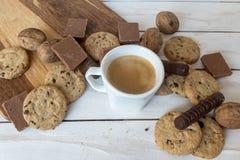Чашка кофе, печенья, грецкий орех и шоколад на белой деревянной предпосылке Стоковое Фото