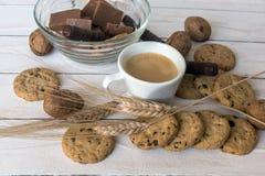 Чашка кофе, печенья, грецкий орех и шоколад на белой деревянной предпосылке Стоковые Изображения