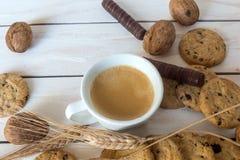 Чашка кофе, печенья, грецкий орех и шоколад на белой деревянной предпосылке Стоковые Фото