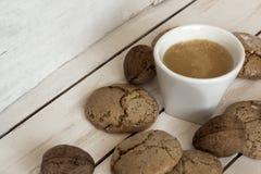 Чашка кофе, печенья, грецкий орех и шоколад на деревянной предпосылке Стоковые Изображения RF