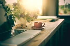 Чашка кофе, печенья и компьтер-книжка на деревянном столе Стоковая Фотография