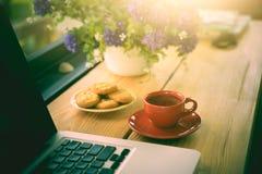 Чашка кофе, печенья и компьтер-книжка на деревянном столе Стоковое Фото