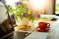 Чашка кофе, печенья и компьтер-книжка на деревянном столе Стоковые Фото