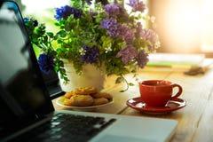 Чашка кофе, печенья и компьтер-книжка на деревянном столе Стоковые Фотографии RF