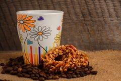 Чашка кофе, печенья и кофейные зерна на деревянной предпосылке Стоковая Фотография