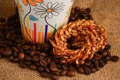 Чашка кофе, печенья и кофейные зерна на деревянной предпосылке Стоковое Изображение
