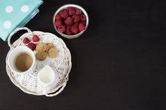 Чашка кофе, печенья кувшин молока на подносе соломы Шар с полениками Черная предпосылка Взгляд сверху Стоковое фото RF