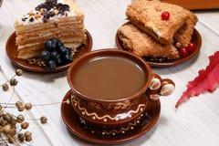 Чашка кофе, печенья плодоовощ, торт и диаграмма красного кота на таблице Белая предпосылка Завод льна сухой Блюда глины sid стоковые фотографии rf