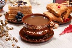 Чашка кофе, печенья плодоовощ, торт и диаграмма красного кота на таблице Белая предпосылка Завод льна сухой Блюда глины sid стоковые фото