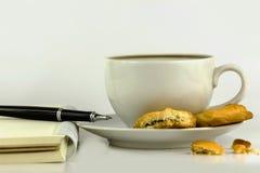 Чашка кофе, печенья, тетрадь и ручка Стоковое фото RF