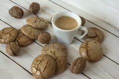 Чашка кофе, печенья macaroons и грецкий орех на деревянной предпосылке Стоковые Изображения