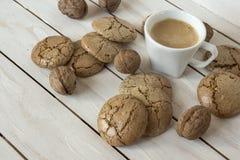 Чашка кофе, печенья macaroons и грецкий орех на деревянной предпосылке Стоковое фото RF