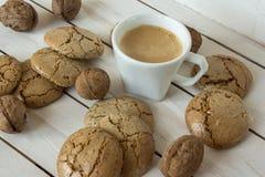 Чашка кофе, печенья macaroons и грецкий орех на деревянной предпосылке Стоковая Фотография
