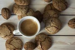 Чашка кофе, печенья macaroons и грецкий орех на деревянной предпосылке Стоковая Фотография RF