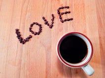 Чашка кофе сидя на деревянной таблице стоковые изображения