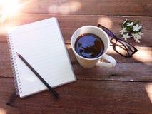 Чашка кофе, стекла, бумага тетради, карандаш и белые цветки на деревянных предпосылке и свете flare Стоковые Фотографии RF