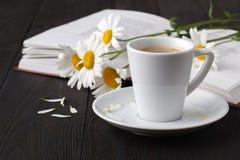 Чашка кофе, стоцвет и книга на деревянном столе стоковые фотографии rf