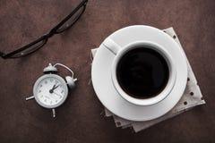 Чашка кофе с будильником на таблице и черных стеклах Стоковая Фотография RF