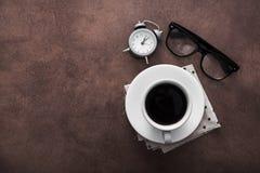 Чашка кофе с будильником на таблице и черных стеклах Стоковые Фотографии RF