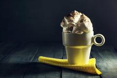 Чашка кофе с взбитой сливк на синей деревянной предпосылке Стоковые Изображения RF