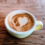 Чашка кофе с картиной сердца в красочной чашке на деревенском сватает Стоковые Изображения