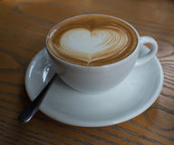 Чашка кофе с картиной сердца в белой чашке на деревянной задней части Стоковая Фотография RF