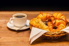 Чашка кофе с круассаном и корзиной торта на заднем плане Стоковая Фотография