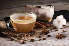 Чашка кофе с молоком и чизкейком на деревянной предпосылке Стоковые Фотографии RF