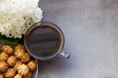 Чашка кофе с печеньями и сиренью на серой ткани Стоковое Фото