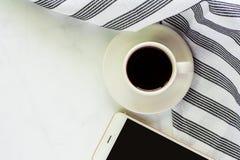 Чашка кофе с поддонником, napery и smartphone на белом мраморе Стоковое Изображение RF