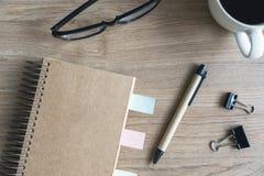 Чашка кофе с пустой тетрадью и notepaper на деревянном столе Стоковые Фото