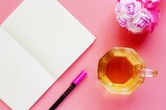 Чашка кофе с раскрытым букетом тетради, ручки и цветка на pi Стоковые Фотографии RF
