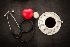 Чашка кофе с стетоскопом и красным сердцем Стоковые Изображения RF