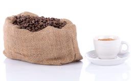 Чашка кофе с сумкой мешковины заполнила с кофейными зернами Стоковая Фотография