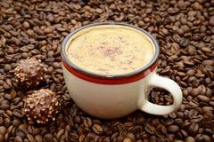 Чашка кофе с циннамоном и конфетами на предпосылке кофейных зерен Стоковая Фотография RF
