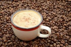 чашка кофе с циннамоном на кофейных зернах подпирает Стоковые Фотографии RF