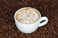 Чашка кофе с циннамоном на предпосылке кофейных зерен Стоковые Фото