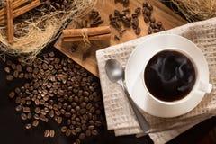 Чашка кофе с чернотой дыма зажарила в духовке зерна и циннамон кофе На деревянной предпосылке Взгляд сверху Стоковые Фотографии RF