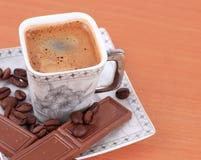 Чашка кофе с шоколадом на таблице Стоковые Фото