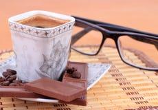 Чашка кофе с шоколадом на таблице Стоковая Фотография RF