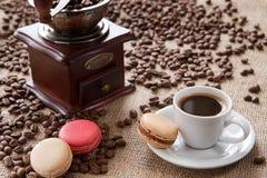 Чашка кофе с macarons на кофейных зернах предпосылки Стоковая Фотография RF