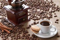 Чашка кофе с macarons на кофейных зернах предпосылки Стоковые Изображения RF