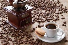 Чашка кофе с macarons на кофейных зернах предпосылки Стоковые Фото