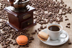 Чашка кофе с macarons на кофейных зернах предпосылки Стоковое Изображение RF