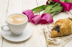 Чашка кофе, тюльпаны, круассан и клубники на деревянной предпосылке Стоковое Фото