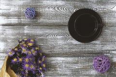 Чашка кофе, цветок обернутый в бумаге kraft на серой таблице сверху Дизайн плоского положения пастельный Скопируйте космос для те стоковые изображения
