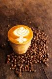 Чашка кофе latte с кофейным зерном на предпосылке деревянного стола Стоковые Фотографии RF