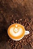 Чашка кофе latte с кофейным зерном на предпосылке деревянного стола Стоковая Фотография